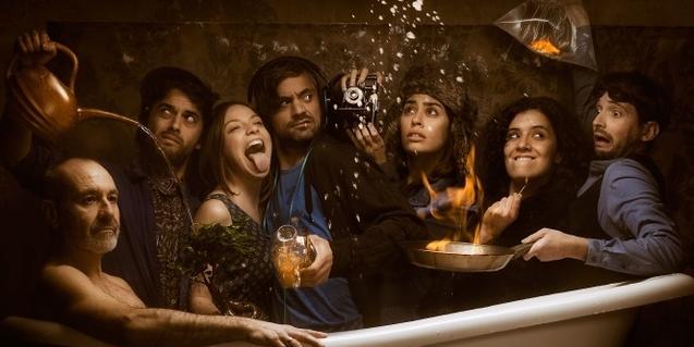 Retrato coral de los miembros de la compañía alrededor de una bañera con un actor en el interior