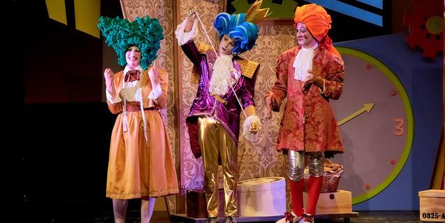 Fotografía del espectáculo, tres actores en el escenario tomando medidas