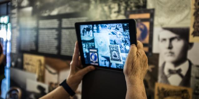 Unes mans fent una foto a un mural amb una tablet
