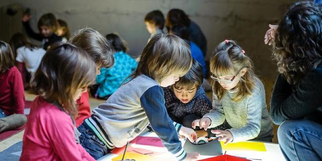 Nens i nenes realitzant el taller amb una taula de llum