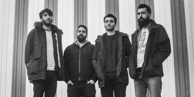 Retrato de grupo en blanco y negro de los cuatro integrantes de la banda
