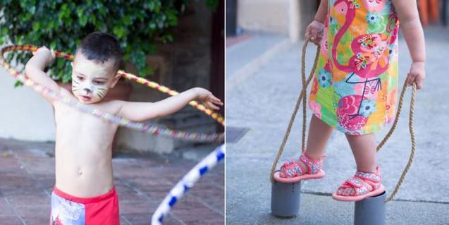 Un niño jugando con un aro y una niña con zancos