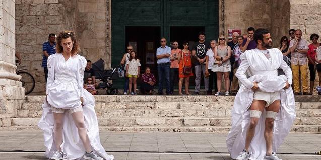 Un home i una dona tots dos vestits de núvia davant la porta d'una església