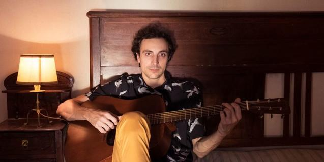 El artista retratado sentado en una cama con una guitarra