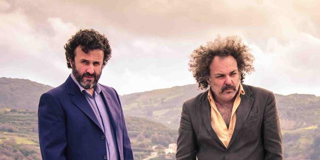 El músic cretenc i el músic australià fotografiats en exteriors amb un paisatge de muntanyes de fons