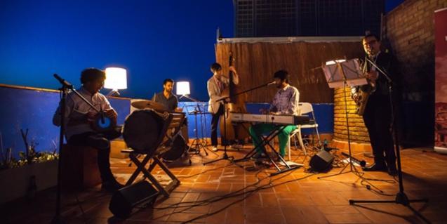 Los cinco músicos de la formación actuando en una azotea durante la noche