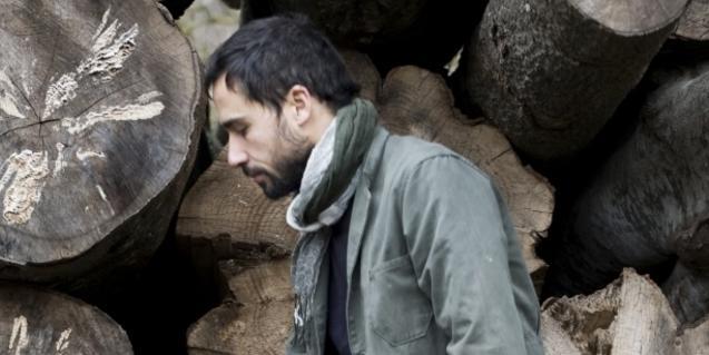 El músic Mau Boada retratat davant d'una pila de troncs