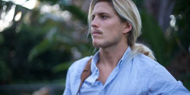 Retrato de plano medio del músico australiano, con el cabello largo recogido en una cola