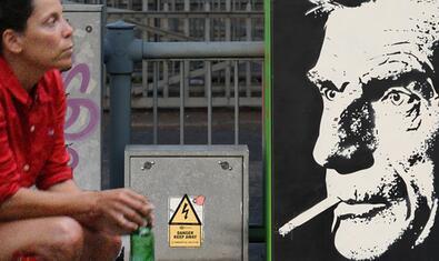 Una noia ajupida es mira una imatge de Samuel Beckett al cartell que anuncia l'activitat