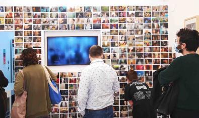 Un grupo de visitantes contempla las imágenes de la muestra el día de la inauguración