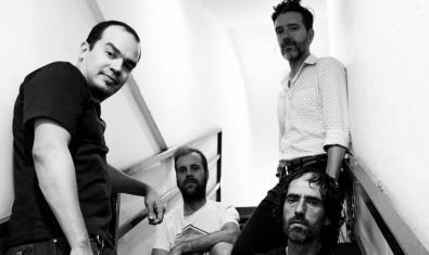 Els quatre membres de la banda retratats en blanc i negre asseguts en una escala