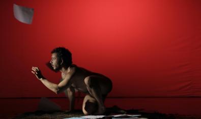 El bailarín Anthony Kmeid agachado y desnudo en un momento de la representación