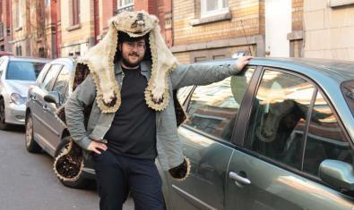 El creador de l'espectacle amb una pell d'animal al cap i recolzat en un cotxe
