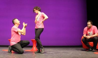 Un actor de rodillas se declara a otro mientras un tercero los contempla sentado en una silla