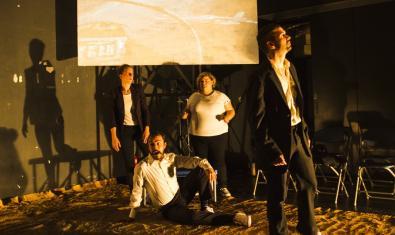 Los actores y actrices de la pieza unos tumbados en el suelo y los otros de pie ante una pantalla de proyecciones