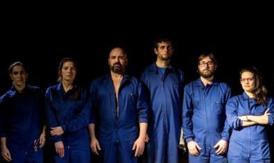 Els integrants de la companyia a l'escenari vestits amb roba de treball de color blau