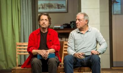 Two actors sitting down, one with a serious look on his face facing forward and the other looking at him.