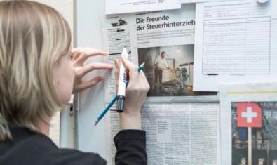 Una dona manipula uns retalls de diari penjats a la paret