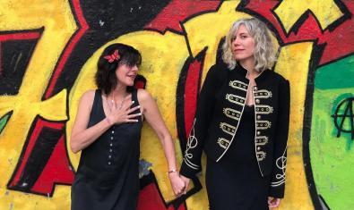 Retrat de les dues artistes agafades de la mà i fotografiades davant d'un mur pintat amb un grafiti