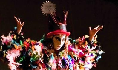 L'artista amb un vestit de plomes de colors i un barret amb una flor durant la representació