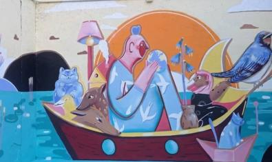 Una vista del mural amb un personatge solcant el mar dins d'una barca carregada de mobles i animals