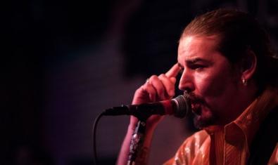 Fotografia del músic en primer pla davant d'un micro en plena actuació