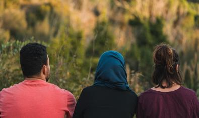 Els tres protagonistes de la funció retratats d'esquenes en un camp amb una de les actrius amb el cap cobert per un mocador