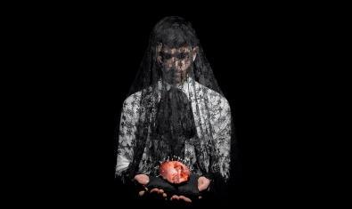 Una figura coberta per un vel sosté un petit coixí amb un cor amb tot d'agulles clavades