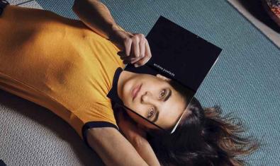 Una noia estirada al terra amb una tableta davant la cara a la pantalla de la qual es veu una fotografia del seu rostre