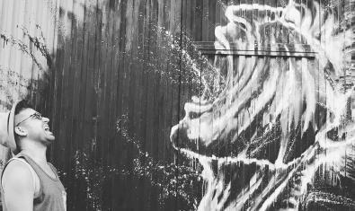 El poeta i raper retratat en blanc i negre fent veure que crida amb la boca oberta davant d'un grafiti que mostra un home que també està cridant amb la boca oberta