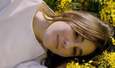 Retrato de Isa Fernández Reviriego alma de este proyecto musical tumbada en el suelo entre flores amarillas