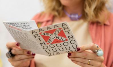"""Una visitant llegint el programa de mà d'""""Art Nou"""""""