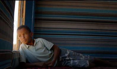 Retrat del nen Bachir estirat i mirant per una finestra