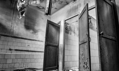 Fotografia en blanc i negre de l'interior d'una antiga fàbrica tèxitil abandonada