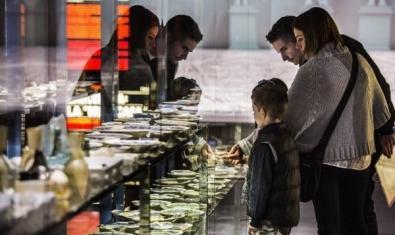 Fotografia de una familia observando una vitrina del museo