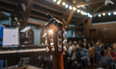 Un primer pla d'una guitarra en una sala plena d'espectadors