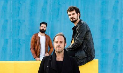 Els tres integrants de la formació retratats asseguts contra un fons de color blau