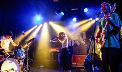 Els tres músics de la formació pujats a l'escenari i sota els focus durant una actuació