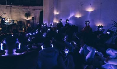 Un aspecte del local durant una actuació a les fosques on l'artista i les persones espectadores porten uns auriculars que emeten llum