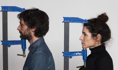 Los dos integrantes de la formación retratados con unas herramientas de construcción en forma de pinza que les sujetan la cabeza