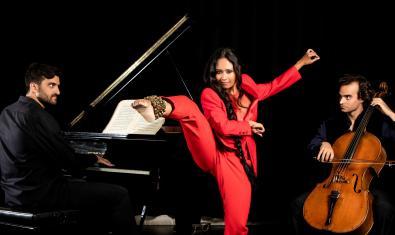 La ballarina índia retratada amb un peu amb cascavells aixecat en l'aire amb els dos músics que l'acompanyen a banda y banda