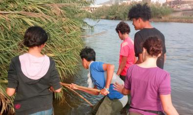 Uns nois i noies fan activitats a la riba del riu Besòs al seu pas pel districte