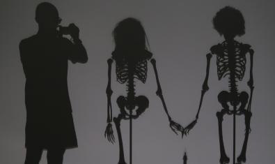 Las sombras de Espinosa y de dos esqueletos cogidos de la mano en una imagen del montaje