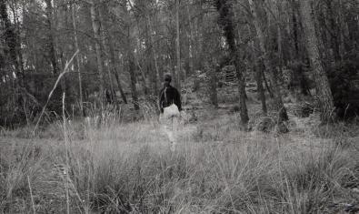 Fotografia en blanc i negre d'una noia d'esquenes en un bosc
