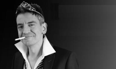 El monologuista retratado en blanco y negro fumando un pitillo y con una corona de princesa puesta