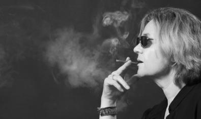 La actriz Anna Güell con gafas de sol y fumando un cigarrillo mientras interpreta a su personaje