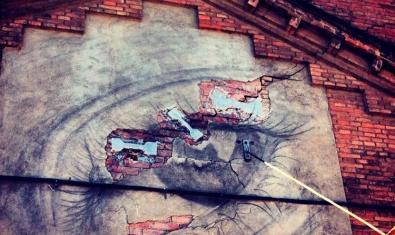 Una fotografia de l'artista que mostra una pintada amb forma d'ull sobre la paret d'un vell edifici del barri