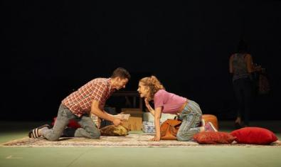 The boy and girl smile at each other, kneeling on a carpet.