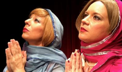 Las dos actrices protagonistas con pañuelos en la cabeza y simulando que rezan