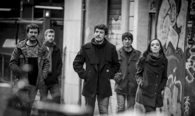 Fotografía en blanco y negro que muestra a los cinco miembros de la banda paseando por una calle con un muro con una pintada de fondo